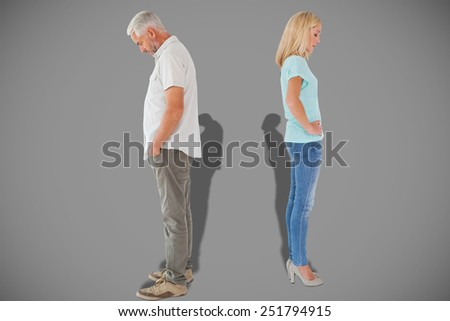 Unhappy couple not speaking to each other against grey - stock photo