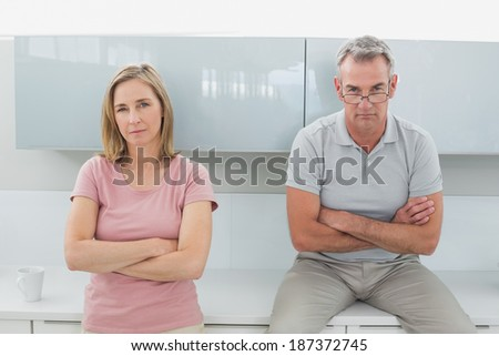 Unhappy couple not talking after an argument in the kitchen at home - stock photo