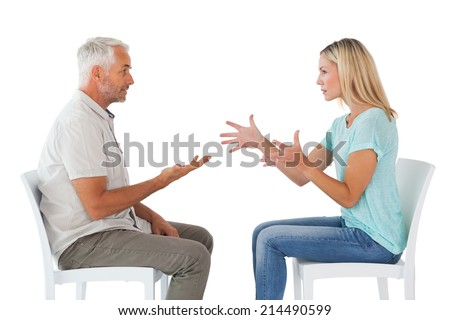 Unhappy couple sitting on chairs having an argument on white background - stock photo