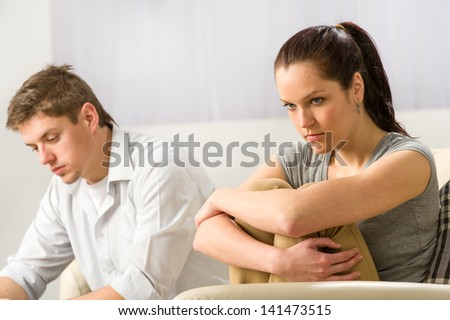 Unhappy couple sitting on couch silently after argument - stock photo
