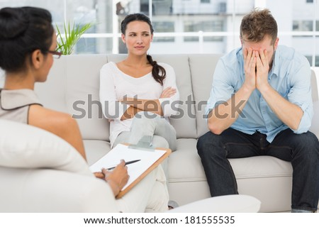 Unhappy couple sitting on sofa at therapy session in therapists office - stock photo