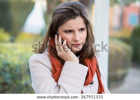 Unhappy customer. Closeup portrait headshot angry young woman talking on mobile phone looking frustrated serious girl student cityscape outdoor background. Multicultural mixt race, asian russian model - stock photo