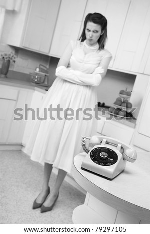 Unhappy cute young woman bride waiting by telephone