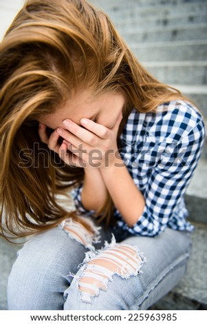 Unhappy depressed teenager with face in hands sitting outdoor - stock photo