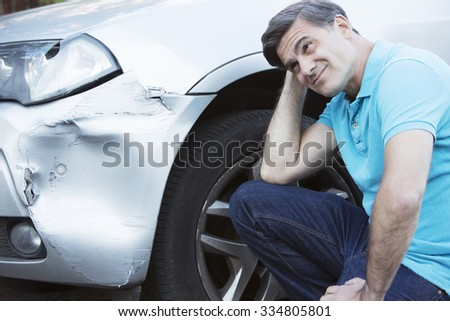 Unhappy Driver Inspecting Damage After Car Accident - stock photo