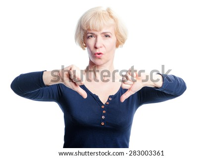 Unhappy elderly woman giving thumbs down gesture looking with negative expression and disapproval. Aged woman isolated on white background. - stock photo