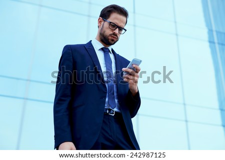 Unhappy employee read text message on cell phone standing against skyscraper office building - stock photo