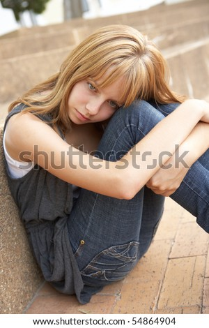 Unhappy Female Teenage Student Sitting Outside On College Steps Using Mobile Phone - stock photo