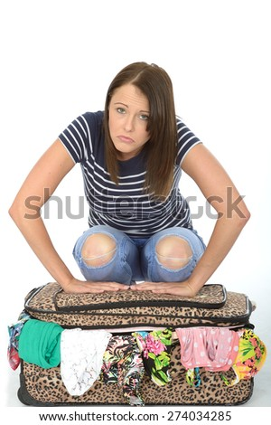 Unhappy Frustrated Upset Attractive Young Woman Sitting on an Overflowing Suitcase - stock photo
