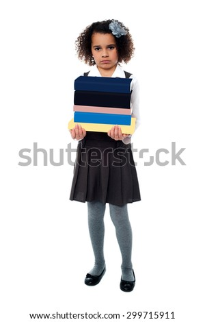 Unhappy girl holding stack of school books - stock photo