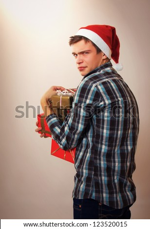 Unhappy greedy young man - Santa Claus holding gift boxes - stock photo