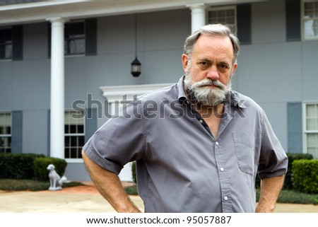 Unhappy homeowner poses in front of his two story columned southern home. - stock photo