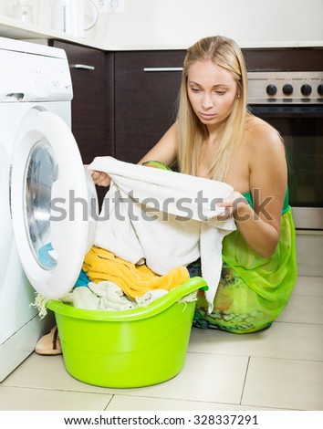 Unhappy  housewife with  clothes near washing machine  - stock photo