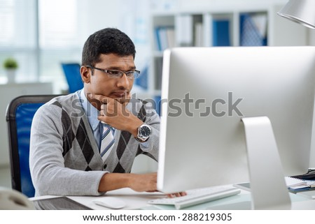 Unhappy Indian programmer looking at computer screen - stock photo