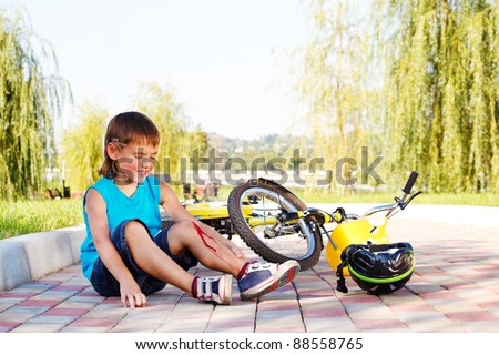 Unhappy kid who has fallen off the bike - stock photo