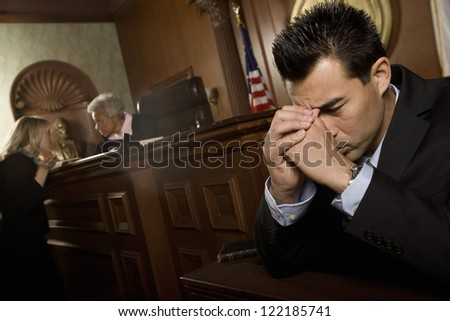 Unhappy lawyer sitting in courtroom - stock photo