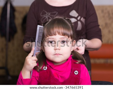 unhappy little girl at barbershop - stock photo