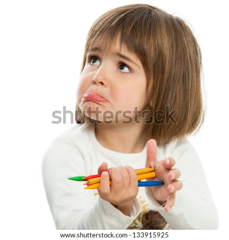 Unhappy little girl holding wax crayons.Isolated. - stock photo
