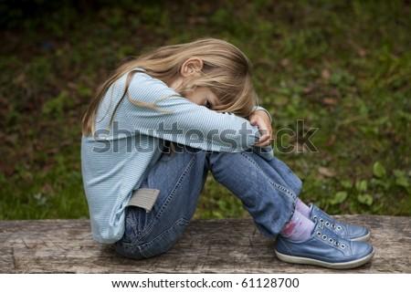 Unhappy little girl sitting on bench in park on autumn - stock photo
