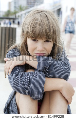 Unhappy little girl sitting on bench. Problems with parents - stock photo