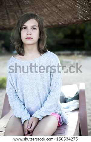 Unhappy little girl sitting on chaise longue  on beach - stock photo