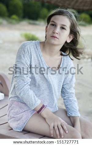 Unhappy little girl sitting on chaise longue  on beach - stock photo