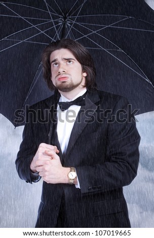Unhappy Man in Suit Holding Umbrella in the Rain and Sighing - stock photo