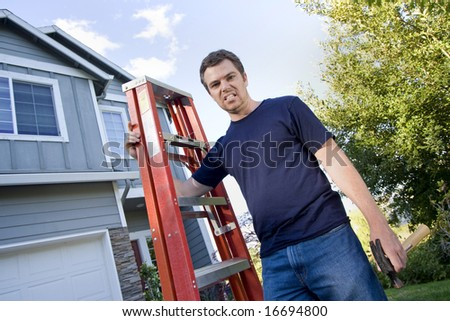 Unhappy man standing in front of house holding ladder and hammer. Horizontally framed photo. - stock photo
