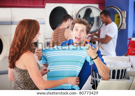 Unhappy man with girlfriend holds a shrunken t-shirt in laundromat - stock photo