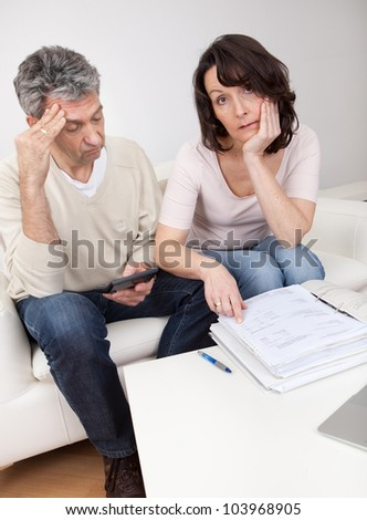 Unhappy mature couple in financial trouble at home - stock photo