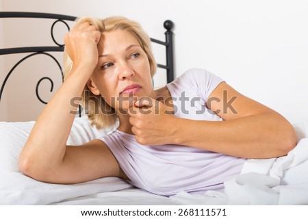 unhappy mature woman laying in bed
