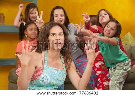 Unhappy mom among wild little girls with hands up in frustration - stock photo