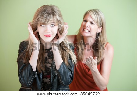 Unhappy mom yells at daughter over green background - stock photo