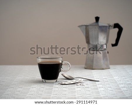Unhappy morning. Black coffee, aspirins and old coffee maker in background. Seems lonely, sad.