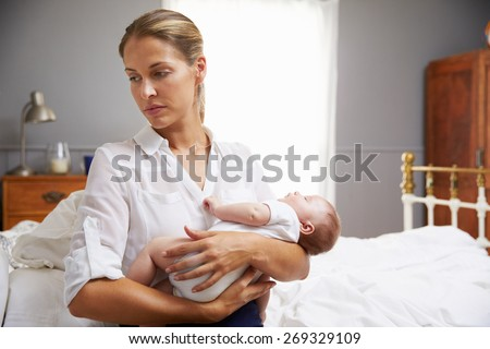 Unhappy Mother Dressed For Work Holding Baby In Bedroom