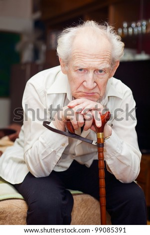 unhappy old man sitting on a bed and holding his cane - stock photo