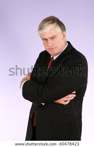 unhappy older business man in suit and tie on purple background - stock photo