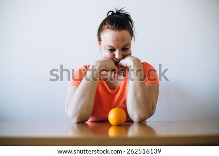 Unhappy overweight woman looking at orange. Diet concept.