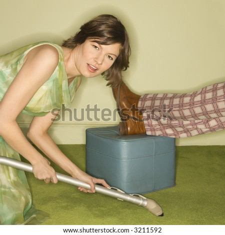 Unhappy pretty Caucasian mid-adult woman kneeling and vaccuuming carpet around male feet resting on foot stool. - stock photo