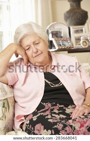 Unhappy Retired Senior Woman Sitting On Sofa At Home - stock photo