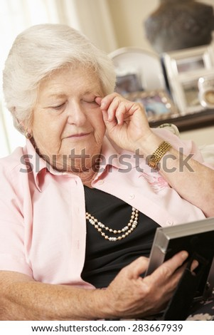 Unhappy Retired Senior Woman Sitting On Sofa At Home Looking At Photograph - stock photo