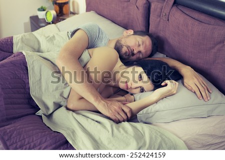 Unhappy sad woman in bed with sleeping boyfriend depressed - stock photo