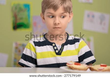 Unhappy schoolboy with healthy breakfast at school - stock photo