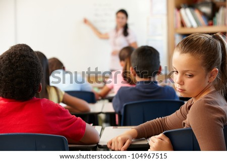 Unhappy schoolgirl in class - stock photo