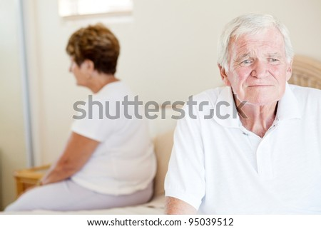 unhappy senior couple sitting on bed - stock photo