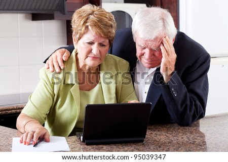unhappy senior couple worrying about expenses at home - stock photo