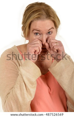 unhappy senior female with both hands in front of her face isolated on white background