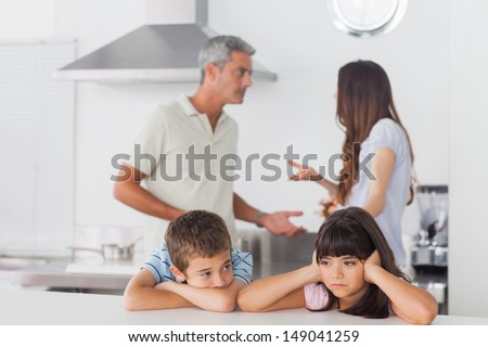 Unhappy siblings sitting in kitchen with their parents who are fighting at home loudly - stock photo