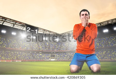 unhappy soccer or football player kneeled down with hands on his face at stadium - stock photo
