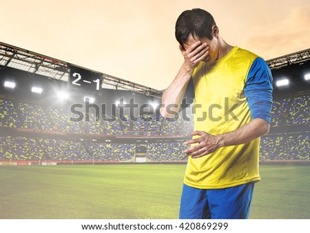 unhappy soccer or football player with palm on his face on stadium - stock photo